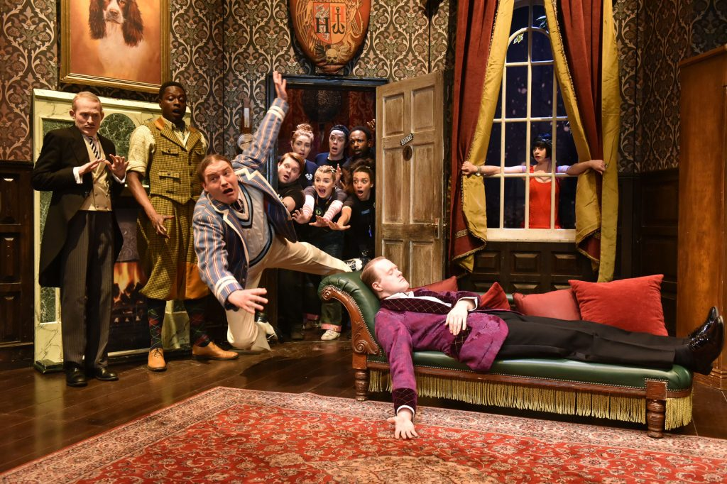 A chaotic scene from The Play That Goes Wrong with a man in a cricket jumper falling into a room, captured in mid-air sailing past another man lying asleep or dead on a chaise longue. Behind them, a group of others cluster round a doorway, staring wide-eyed into the room.